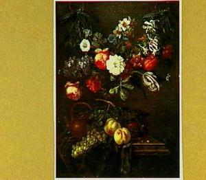 Theepot, vruchten en gedrapeerd kleed op tafel onder bloemenguirlande