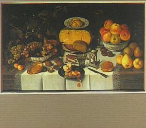 Stilleven met vruchten, kazen, drinkgerei, brood, een zoutvat en een mes, op een damasten laken