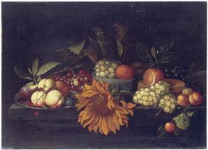 Perziken en een vijg op een tinnen bord, druiven en een sinaasappel in een Wan Li-kom, een spanen doos en een zonnebloem op een tafel