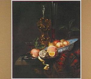 Stilleven met siervaatwerk en vruchten op een tafel met een oosters kleed