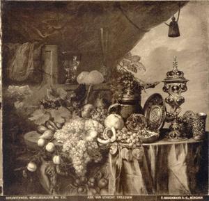 Stilleven met pronkzilver, glaswerk en vruchten, met rechts een doorkijk naar buiten