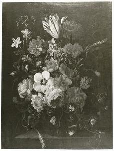 Bloemen en een tak met bramen in een glazen vaas op een stenen plint
