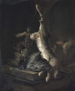 Opgehangen dode haas en gevogelte op een stenen plint