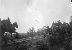 Militairen te paard met een kanon tijdens een militaire manoeuvre