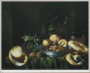 Stilleven met vruchten en noten in een Wan Li-schaal, een citroen, drinkglazen en brood op een tafel