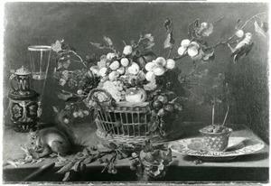 Een stillleven met groente, fruit en een eekhoorn op een tafel, met rechtsboven een papagaai aan een tak