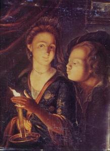 Een vrouw met een kaars die een jongen probeert uit te blazen