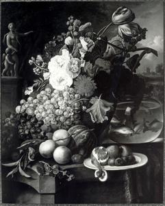 Stilleven met vruchten en bloemen, een beeldje en een kom goudvissen, voor een landschap