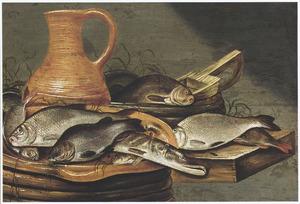 Stilleven van een kan van rood aarderwerk en vis op een houten blad