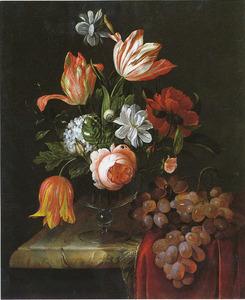 Bloemen in een glazen vaas met een druiventros op een deels bedekt marmeren blad