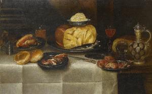 Kaas, ham, brood, krabben, twee glazen wijn en een steengoed kan op een gedekte tafel