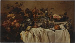 Stilleven met een pronkbeker, een liggende tinnen kan, vruchten, een ham op een tinnen schotel, een zoutvat en drie roemers