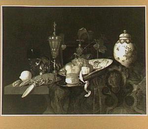Stilleven met kreeft, drinkgerei, pronkzilver, fruit en een porseleinen dekselvaas op een oosters kleed