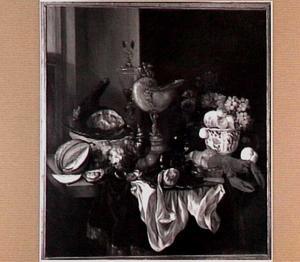 Pronkstilleven met nautilusbeker, vruchten, kreeft en gebraad, sierglas- en vaatwerk op een donker kleed met wit servet