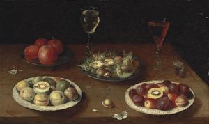 Hazelnoten, walnoten en fruit op schalen en twee wijnglazen op een houten tafel