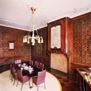 Wethouderskamer voorzien van wand- en plafondarfwerking in rococo-stijl en goudleerbehang