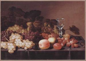 Stilleven van druiven, pruimen, bessen en een appel met een wijnglas op met een kleed bedekte tafel