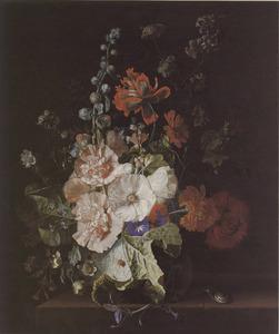 Stokroos en andere bloemen in een glazen vaas