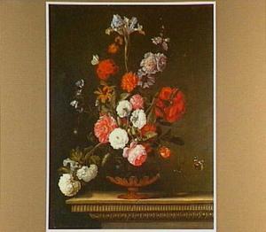 Bloemen in een geornamenteerde glazen vaas op een geprofileerde plint