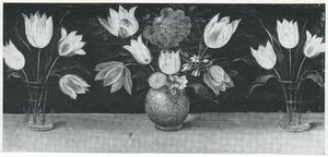 Twee bekers en een steengoed vaas met bloemen op een houten blad