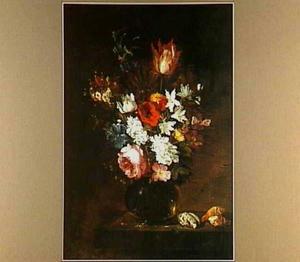 Bloemen in een glazen vaas naast drie schelpen