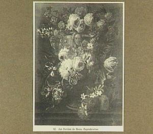 Bloemen gerangschikt om een tuinvaas op een stenen plint