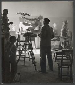 Han Wezelaar in zijn atelier, op de achtergrond model van het bevrijdingsmonument Roozendaal