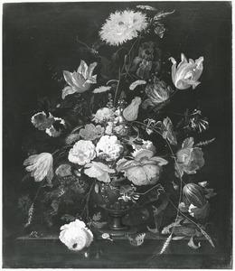 Bloemen in een metalen vaas in een nis