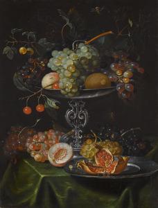 Tazza met vruchten en tinnen bord met granaatappel op een gedekte tafel