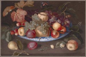Vruchten in en voor een porseleinen schaal met een sprinkhaaan