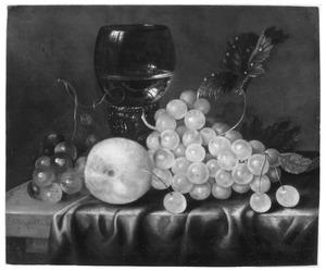 Vruchten rondom een roemer op een gedekte tafel