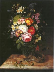 Boeket bloemen in een glazen vaas op een marmeren tafelblad