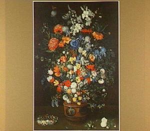 Groot boeket in een gedecoreerde vaas, ernaast een bloemenkrans en losse bloemen