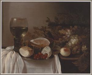 Stilleven met vruchten, een roemer, een ham en een broodje op een deels gedekte tafel