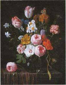 Bloemen in een glazen vaas op een stenen tafel met een bruin tafelkleed