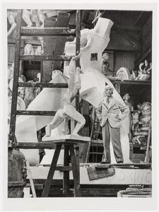 Ossip Zadkine staand voor het gipsmodel van zijn beeld De verwoeste stad in de gieterij Rudier te Parijs