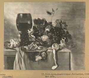 Stilleven met vruchten, roemer en brood op een donker kleed
