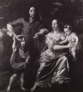Familieportret van een man en zijn vrouw met hun twee kinderen in een park