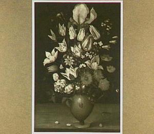 Bloemstuk in een stenen vaas met een klein masker op een houten plint