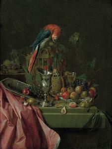 Stilleven met pronkvaatwerk en een papegaai op een mand met vruchten