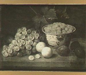 Stilleven van aardbeien in een porseleinen kom, op de voorgrond een tros druiven en een aantal pruimen