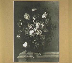 Boeket van bloemen in een glazen vaas op en stenen plint