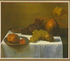 Stilleven van een bord met brood en kersen, een bord met kastanjes, druiven en een pompoen op tafel