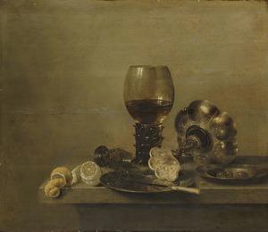 Stilleven met roemer met wijn, een gebroken glas, een omgevallen tazza en twee citroenen