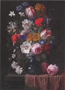 Bloemen in een glazen vaas, met een roos, op een deels gedekte stenen plint
