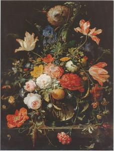 Bloemen en een tak met sinaasappel in een glazen vaas op een stenen plint