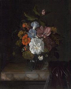 Bloemen in een glazen vaas op een deels gedekte marmeren blad