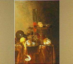 Stilleven met citroen, druiven, glas- en zilverwerk en een stuk brood op een donker kleed