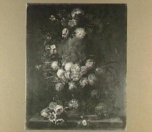 Bloemstilleven rond een geornamenteerde tuinvaas met de drie gratieën op een stenen plint