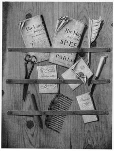 Brievenbord met kranten, een schaar, schrijfgerei en een kam